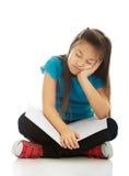 Kleines Mädchen, das queresmit beinen versehenes und das Lernen sitzt Stockfoto