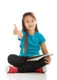 Kleines Mädchen, das queresmit beinen versehenes und das Lernen sitzt Stockbilder