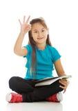 Kleines Mädchen, das queresmit beinen versehenes und das Lernen sitzt Stockbild
