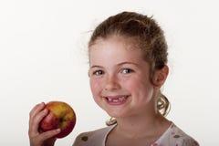 Kleines Mädchen, das roten Apfel isst Lizenzfreies Stockbild