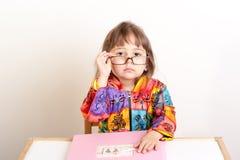 Kleines Mädchen, das am Schreibtisch sitzt und über ihren Gläsern schaut Stockfotografie