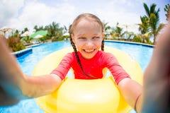 Kleines Mädchen, das selfie am aufblasbaren Gummiring hat Spaß im Swimmingpool macht Lizenzfreie Stockfotos