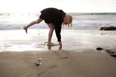 Kleines Mädchen, das Shells am Strand montiert Stockfoto