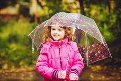 Kleines Mädchen, das unter einem Regenschirm vom Regen im Herbstpark sich versteckt Stockfotografie