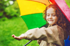 Kleines Mädchen, das unter einem Regenschirm vom Regen sich versteckt Lizenzfreie Stockfotos