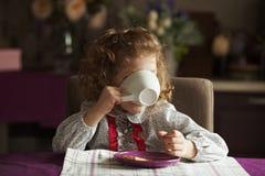 Kleines Mädchen, das von einem großen weißen Cup trinkt Stockfoto