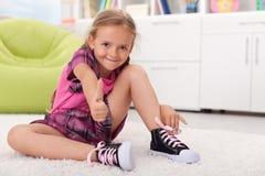 Kleines Mädchen, das wie man ihre Schuhe lernt, bindet Stockfoto