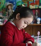 Kleines Mädchen, das zu Hause Heimarbeit tut Lizenzfreies Stockfoto
