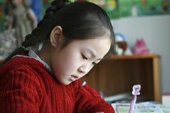 Kleines Mädchen, das zu Hause Heimarbeit tut Stockbilder