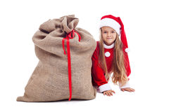 Kleines Mädchen in der Weihnachtsausstattung, die hinter Sankt-Tasche sich versteckt Lizenzfreies Stockbild