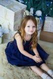 Kleines Mädchen in einem eleganten Kleid, welches die Kamera sitzt und betrachtet Lizenzfreie Stockbilder