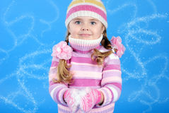 Kleines Mädchen in einer Strickjacke mit dem Schnee Lizenzfreie Stockfotos
