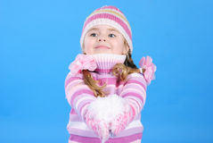 Kleines Mädchen in einer Strickjacke und in einem Hut mit dem Schnee Stockbilder