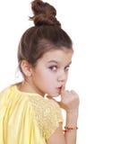 Kleines Mädchen hat Zeigefinger zu den Lippen als Zeichen der Ruhe gesetzt Stockbild