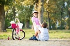 Kleines Mädchen hilft Jungen mit Rollschuhen, oben zu stehen Lizenzfreies Stockbild