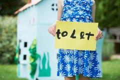 Kleines Mädchen-Holding, zum des Zeichens außerhalb des Spiel-Hauses zu lassen Lizenzfreie Stockbilder