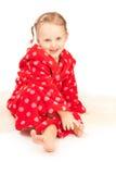 Kleines Mädchen im roten Hausmantel, der auf Fußboden sitzt Lizenzfreie Stockfotografie