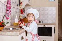 Kleines Mädchen im Schutzblech in der Küche Stockbilder