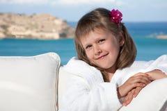 Kleines Mädchen im weißen Bademantel, der auf Terrasse sich entspannt Lizenzfreie Stockbilder