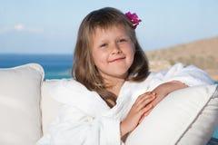 Kleines Mädchen im weißen Bademantel, der auf Terrasse sich entspannt Stockbilder