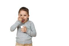 Kleines Mädchen isst den Jogurt, der auf weißem Hintergrund lokalisiert wird Stockfotos