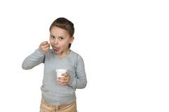 Kleines Mädchen isst den Jogurt, der auf weißem Hintergrund lokalisiert wird Lizenzfreie Stockfotografie