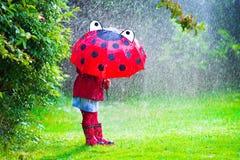 Kleines Mädchen mit dem Regenschirm, der im Regen spielt Lizenzfreies Stockbild