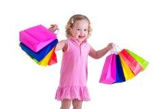 Kleines Mädchen mit Einkaufstaschen Stockbilder