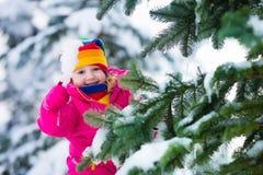 Kleines Mädchen mit Eiszapfen im Park des verschneiten Winters Lizenzfreie Stockfotos