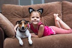 Kleines Mädchen mit Katzengesichtsmalerei-Umarmungshund Stockbild