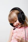 Kleines Mädchen mit Kopfhörern Stockfotos