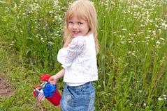 Kleines Mädchen mit patriotischem Blumenstrauß im roten Eimer Lizenzfreies Stockbild