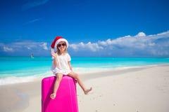 Kleines Mädchen in Sankt-Hut, der auf einem großen Koffer am tropischen Strand sitzt Stockfoto