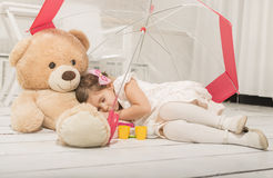 Kleines Mädchen sleepingin unter umbrela in ihrem Teddybären tragen Waffen Stockfotos