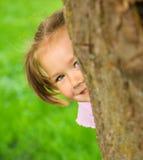 Kleines Mädchen spielt Verstecken draußen Stockfoto