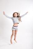 Kleines Mädchen springt auf einen weißen Hintergrund Lizenzfreies Stockfoto