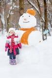 Kleines Mädchen steht und singt vor großem Schneemann Lizenzfreie Stockbilder