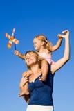 Kleines Mädchen und Frau mit einem Pinwheel spielen draußen Stockfotografie
