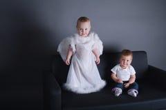 Kleines Mädchen und Junge im Engelskleid Stockbilder