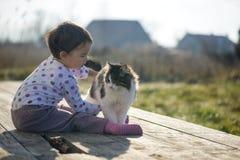 Kleines Mädchen und Katze spielen außerhalb nahe des Hauses Lizenzfreies Stockbild