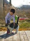 Kleines Mädchen und Katze spielen außerhalb nahe des Hauses Stockbild