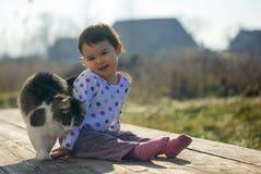 Kleines Mädchen und Katze spielen außerhalb nahe des Hauses Lizenzfreie Stockfotos