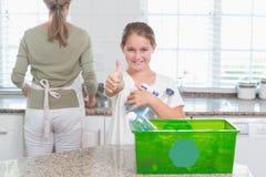 Kleines Mädchen, welches die Wiederverwertung von Flaschen mit den Daumen oben hält Stockfoto