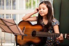 Kleines Mädchen während einer Gitarrenlektion Stockfoto