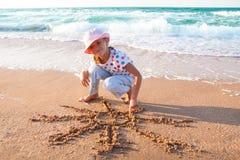 Kleines Mädchen zeichnet Sonne auf Sand am Strand Lizenzfreie Stockfotos