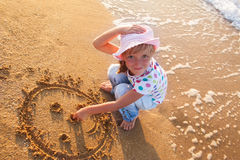 Kleines Mädchen zeichnet Sonne auf Sand am Strand Stockbild