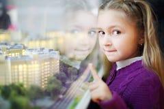 Kleines Mädchen zeigt auf Plan von Wohngebäuden. Stockfotos