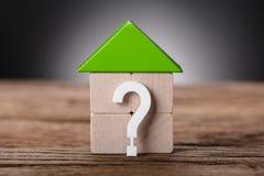 Kleines Modell House By Question Mark On Wood lizenzfreie stockbilder