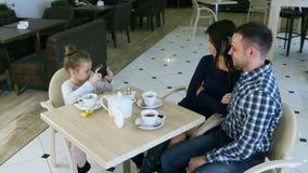 Kleines modernes Mädchen macht Fotos ihrer reizenden Eltern im Café stock video footage