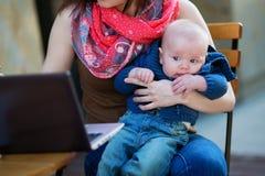 Kleines 4-monatiges Baby in den Armen seiner Mutter Stockbilder